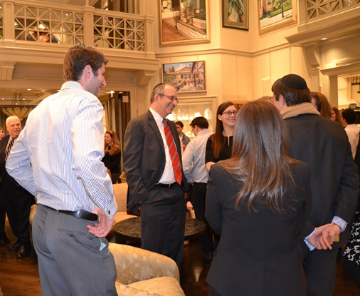 Dr. Alan Kadish (center, red tie), president and CEO of Touro College, speaks with young professionals at a cocktail reception at the home of Carol Feinberg and Ken Gilman in Manhattan.
